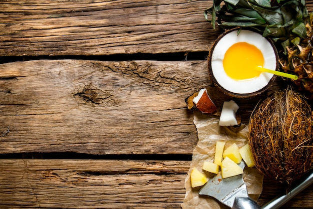 Koktajl pina colada. świeży koktajl w filiżance rumu kokosowego i ananasa na drewnianym stole. wolne miejsce na tekst. widok z góry