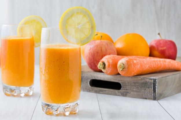 Koktajl pomarańczowy, jabłko i marchewka na biały drewniany stół