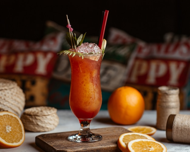 Koktajl soku pomarańczowego wewnątrz szklanki z kostkami lodu i ziołami.
