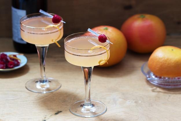 Koktajl szampański z sokiem grejpfrutowym, udekorowany skórką i malinami. styl rustykalny.