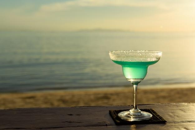Koktajl szklany margarita na plaży o zachodzie słońca
