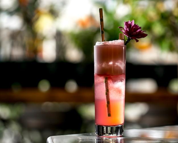 Koktajl szklany przyozdobiony słomką z kwiatów i papieru w pobliżu tarasu