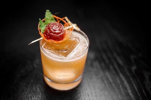 Koktajl szklany wypełniony dekorowanym pomarańczowym koktajlem alkoholowym