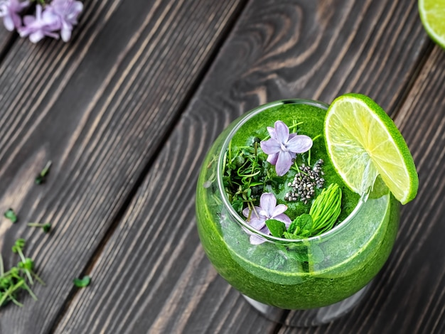 Koktajl szpinakowy z owocami i nasionami, ozdobiony liśćmi mięty, plasterkiem limonki i polnymi kwiatami w szklanym kubku