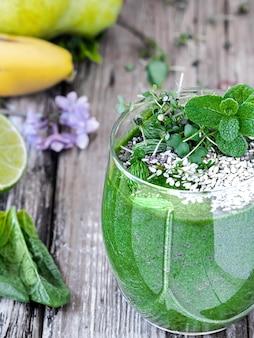 Koktajl szpinakowy z owocami i nasionami superfoods, ozdobiony liśćmi mięty w szklanym kubku