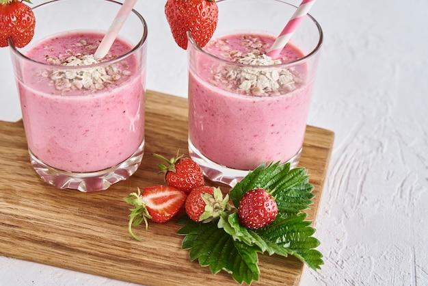 Koktajl truskawkowy w szklance ze słomką i świeżymi jagodami