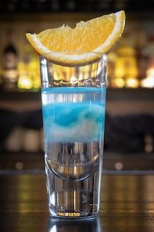 Koktajl w chmurze, z plasterkiem pomarańczy na blacie barowym