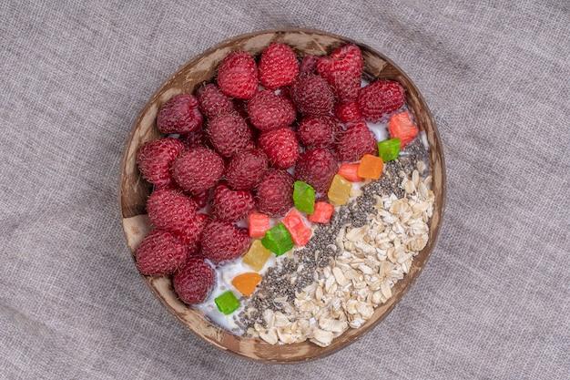 Koktajl w misce kokosowej z malinami, płatkami owsianymi, kandyzowanymi owocami i nasionami chia na śniadanie, z bliska. pojęcie zdrowego odżywiania, pożywienie. widok z góry