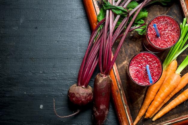 Koktajl warzywny z burakami i marchewką. na czarnym tle.
