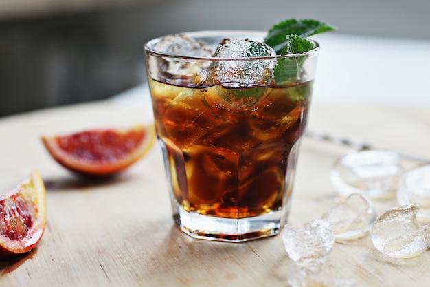 Koktajl whisky cola z lodem w szklance. na drewnianej desce są fragmenty owoców. zdjęcie z głębią ostrości.