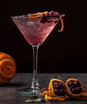 Koktajl wiśniowy przyozdobiony skórką z wiśni i pomarańczy oraz lodem