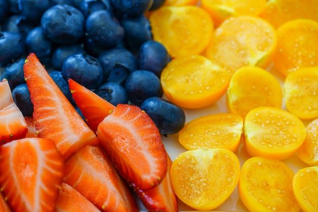 Koktajl witaminowy z jagód i owoców. truskawki, jagody, rozmaryn i pęcherzyca. ozdoba na świąteczne ciasto z naturalnymi produktami.