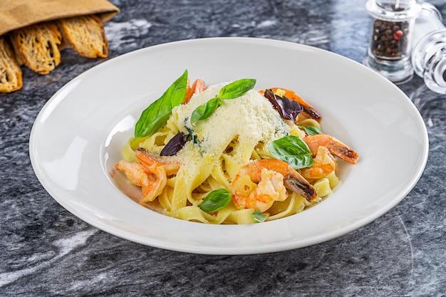 Koktajl włoskiej restauracji. makaron aglio olio z owocami morza: krewetki, bazylia, parmezan. z bliska na pyszne domowe spaghetti podawane na marmurowym stole. włoskie jedzenie na lunch