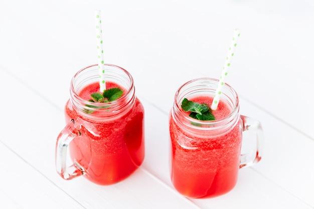 Koktajl z arbuza jako zdrowy napój na lato. arbuz w szklanym słoju kamieniarzu na drewnianym tle.