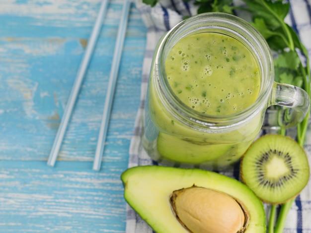 Koktajl z awokado z pokrojonymi owocami kiwi, awokado i ziołami. dieta wegetariańska. surowe jedzenie.