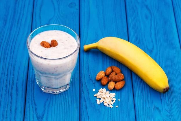 Koktajl z bananów i mleka migdałowego w szklanej, niebieskiej ścianie