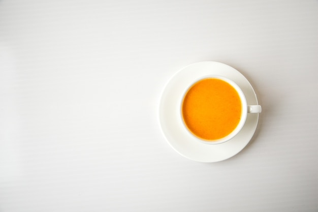 Koktajl z dyni, latte z przyprawami. boozy koktajl w filiżance biały na białym tle. jesienne sezonowe gorące napoje. święto dziękczynienia. widok z góry