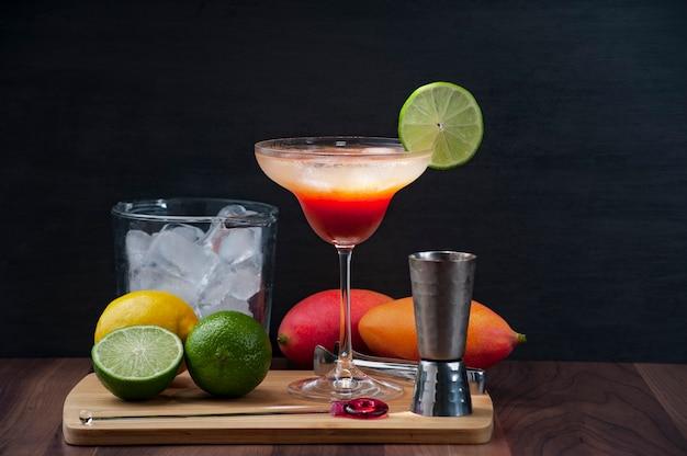 Koktajl z mango, wódki, cytryny i lodu na drewnianej desce w towarzystwie wiaderka z lodem