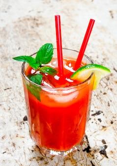 Koktajl z pomidorów, wódki, lodu, limonki, pieprzu, soli na rustykalnym tle.