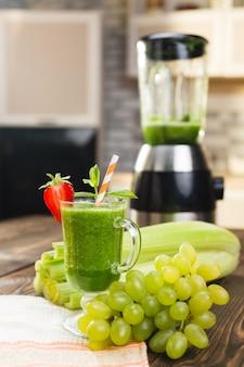Koktajl ze świeżych owoców i warzyw na stole w kuchni w szkle
