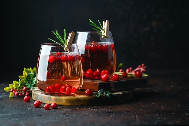 Koktajl żurawinowy z rozmarynem w dwóch szklankach na ciemny.
