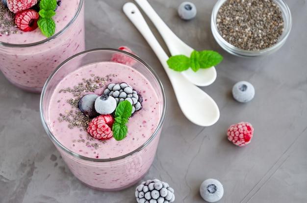 Koktajle jagodowe z jogurtu, nasion chia i mrożonych jagód w szklance na ciemnym tle betonu. zdrowe jedzenie.