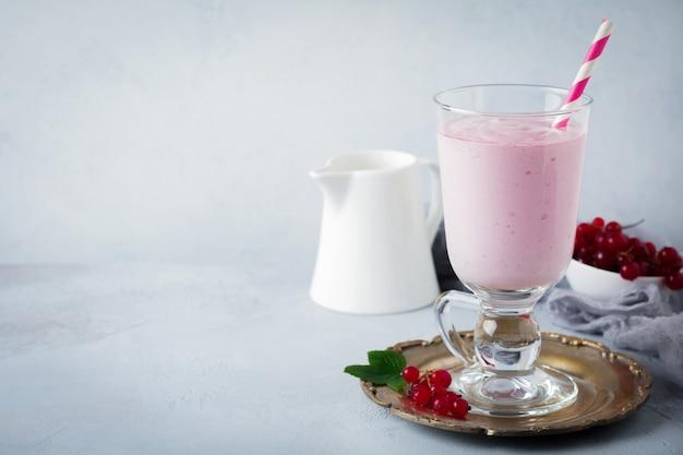 Koktajle jogurtowe z czerwonej porzeczki, koktajl mleczny w szklanym kubku na szarej betonowej powierzchni. selektywna ostrość. skopiuj miejsce