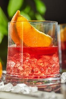 Koktajle negroni z plastrami pomarańczy i lodu