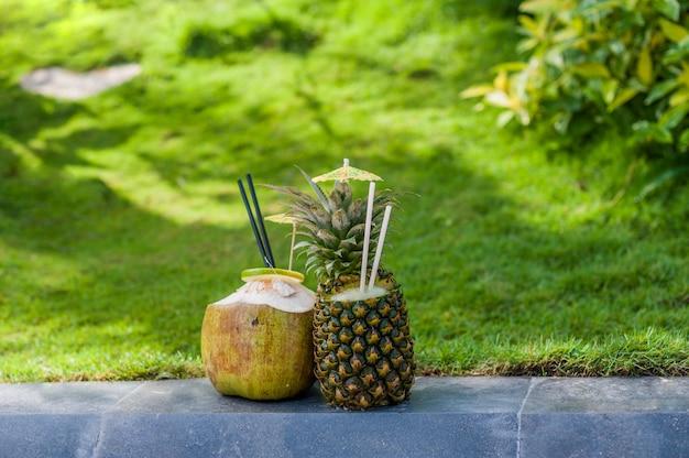Koktajle owocowe z ananasa i kokosa na tle zielonej trawy