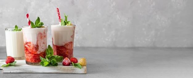 Koktajle truskawkowe i malinowe w szklankach ozdobione są miętą i malinami