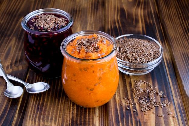 Koktajle warzywne lub puree z nasionami lnu w szklanych słoikach na drewnianej powierzchni