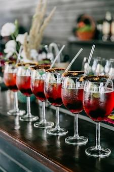Koktajle z czerwonego wina sangria z rzędu na ladzie barowej z owocami cytrusowymi