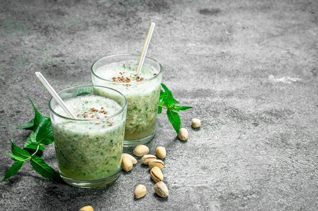 Koktajle z miętą, pistacjami i mlekiem kokosowym. na tle rustykalnym.