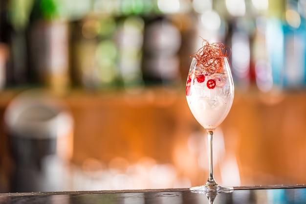 Koktajle z tonikiem ginu w kieliszku do wina z chili na blacie barowym w pup lub restauracji.