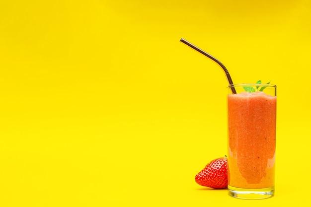 Koktajle z truskawkami w szklanym kieliszku, na żółtym tle z miejscem na kopię, koncepcją zdrowego stylu życia i diety