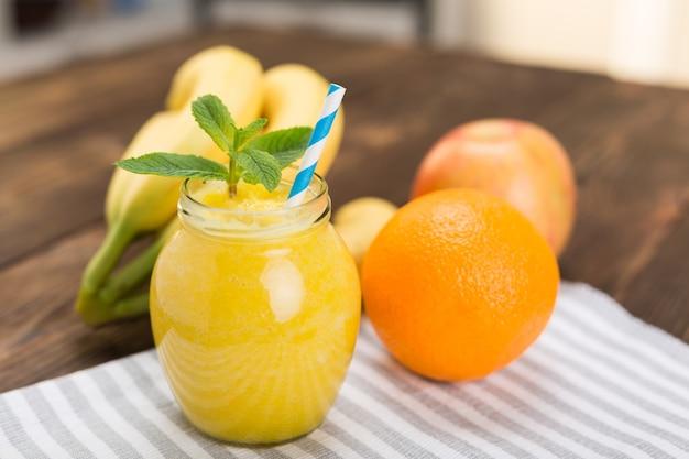 Koktajle ze świeżych owoców na stole w kuchni w małym słoiku