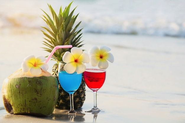 Koktajli / lów szkła z koksem i ananasem na czystej piasek plaży - owoc i napój na morze plaży