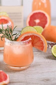 Koktajlowy różowy palomas świeża limonka i rozmaryn w połączeniu ze świeżym sokiem grejpfrutowym i tequilą