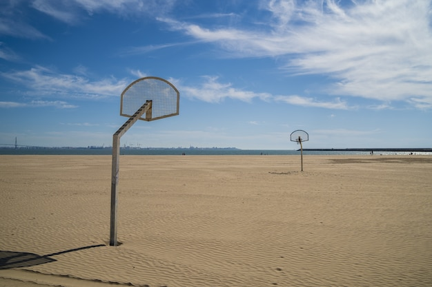 Koła do koszykówki na plaży z zachmurzonym błękitnym niebem