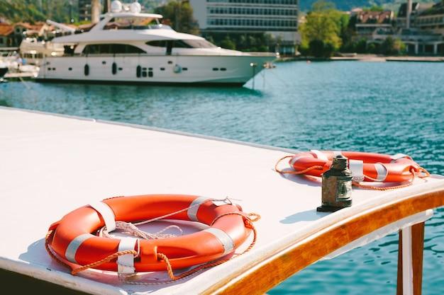 Koła ratunkowe leżą na dachu łodzi, na molo w pobliżu starego miasta kotor w czarnogórze, naprzeciwko