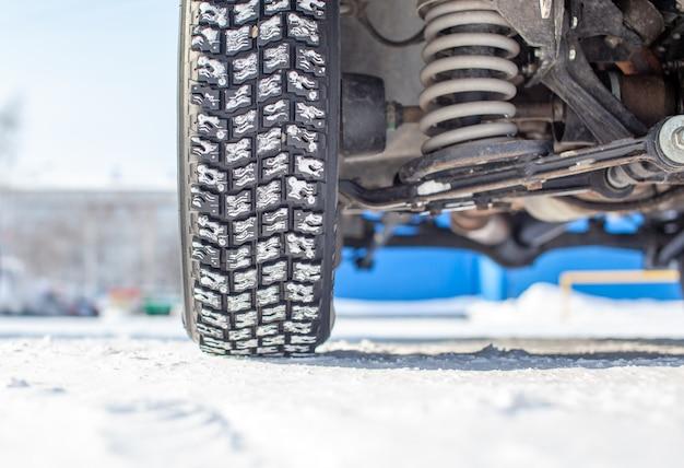 Koła samochodu na śniegu w zbliżeniu zimy. widoczne jest zawieszenie i podwozie samochodu. samochód jest zaparkowany na zaśnieżonym parkingu.
