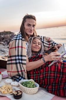 Kolacja na plaży. urocza szczęśliwa para czuje się niesamowicie podczas romantycznej kolacji z winogronami i serem na plaży