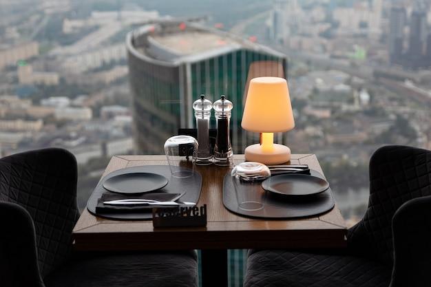Kolacja o zachodzie słońca z panoramicznym widokiem na centrum biznesowe moskwy. kolacja na tle miasta. restauracja z widokiem na centrum miasta. romantyczna sceneria, moskwa, rosja
