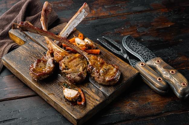 Kolacja przy grillu. grillowane kotlety mięsne jagnięce z zestawem cebuli i tymianku, na drewnianej desce do serwowania, na starym ciemnym tle drewnianego stołu