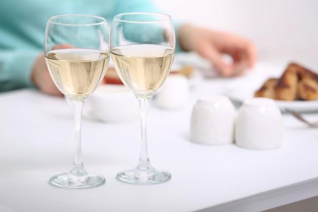 Kolacja z kieliszkami wina na jasnym rozmytym tle