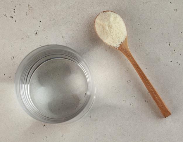 Kolagen w postaci białego proszku na drewnianej łyżce i szklance wody