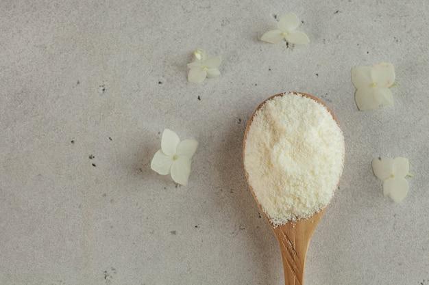 Kolagen w postaci białego proszku na drewnianej łyżce