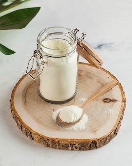 Kolagen w postaci białego proszku w szklanym słoiczku i na drewnianej łyżce pielęgnuje skórę odmładzanie