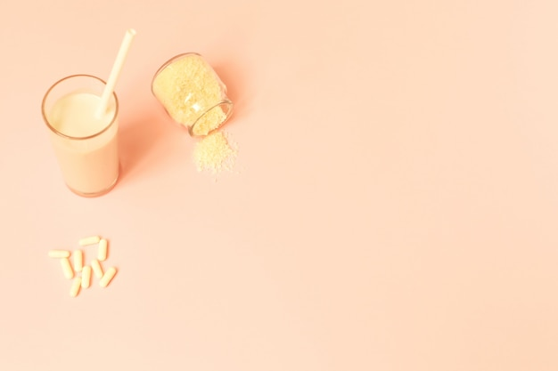 Kolagen w proszku, mleko i pigułki na różowym tle.