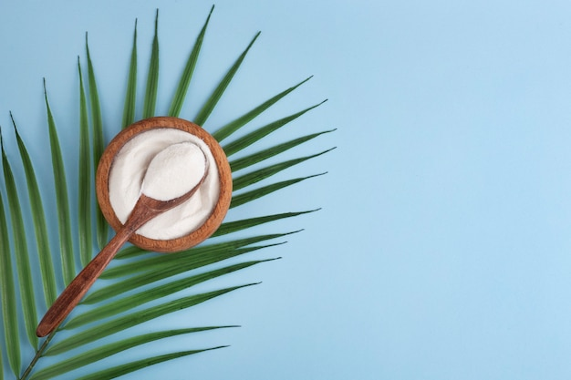 Kolagen w proszku w drewnianej misce, łyżka, niebieska przestrzeń, widok z góry, zielony liść